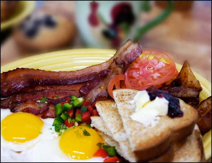 colorful breakfast platter with eggs, bacon and toast