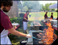 flames are shooting up the grills at a catered corporate bbq on Long Island