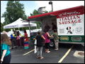our carnival style italian sausage and pepper truck is surrounded by people at a catered event on Long Island