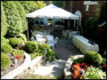 small white party tent and tables set in a back yard for a private catered party