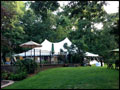 beautiful party tent and umbrella tables set in a backyard for party catering to offer shade in a hot summer day