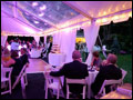 Wedding guests sitting at their tables in a wedding tent with clear ceiling and rope lights, next to the dance floor and cupcake tower