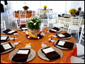 Tables are decorated with mums and pumpkins and set in autumn colors for a catered outdoor wedding in New York