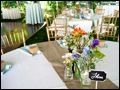 tables are set in mint and burlap with wild flowers in mason jars for a catered backyard wedding on Long Island