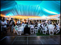 Long Island wedding party with Tuscan Style catering in full swing in a lit party tent featuring a black dance floor