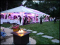 catered Long Island wedding with a party tent set up in the back yard and a lit bonfire