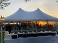 Sun is setting over a waterfront wedding tent